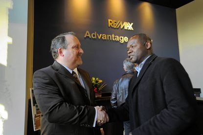 Re/Max Branch Manager Wayne Curtis (left) greets real estate agent Jenell Forman during the opening of a Re/Max Advantage Realty office.