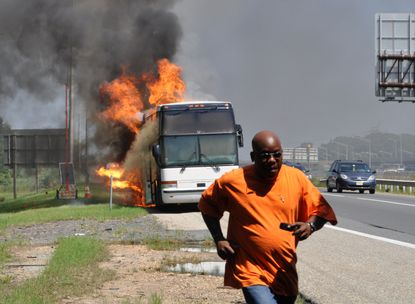 """Simon Fitzgerald, a passenger on the New York to Baltimore bus that caught fire on the New Jersey Turnpike, said he took this photo, """"when the fire caught the fuel tank and the driver, who had been on the phone, turned to run farther from the bus."""""""