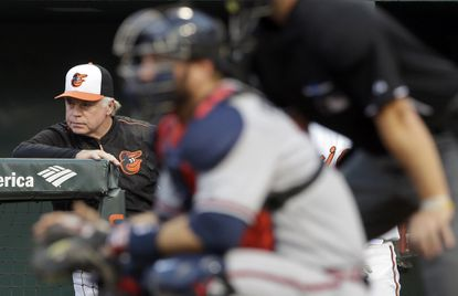Orioles manager Buck Showalter, left, is seen past Atlanta Braves catcher A.J. Pierzynski and home plate umpire Scott Barry as he watches from the dugout in the first inning, Tuesday, July 28, 2015, in Baltimore.