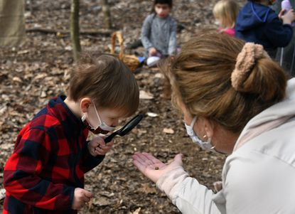 Shepherd Hines-Gauvin, 3, uses a magnifying glass to look at a seed in the Notchcliff Nature Program forest preschool, a project of the Eastern Region Association of Forest and Nature Schools. Children from ages 3-7 attend the program, which is all outdoors, and is held on the grounds of Glen Meadows Retirement Community. Lead teacher Lisa Mullaney is on right.