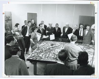 Jim Rouse, center with glasses and arms folded, presents plans for Columbia as well as a model of Town Center and the first village to the Howard County commissioners and other county officials Nov. 11, 1964.