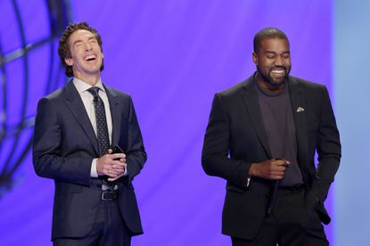 With their eyes closed for prayer, Joel Osteen, left, and Kanye West laugh as West makes a joke while leading the prayer during a service at Lakewood Church on Nov. 17, 2019, in Houston.