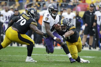 Baltimore Ravens quarterback Lamar Jackson (8) scrambles between Pittsburgh Steelers defensive linemen Javon Hargrave (79) and Cameron Heywardin the second half of an NFL football game, Sunday, Oct. 6, 2019, in Pittsburgh. The Ravens won 26-23. (AP Photo/Don Wright)