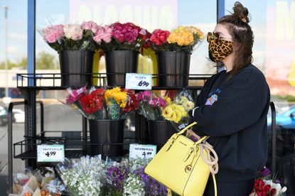 Deanna Runyon wears a cloth face mask as she waits in line at Trader Joe's in Annapolis. Many in the Annapolis area are taking heed and wearing facial coverings and masks when out in public to help with COVID-19 mitigation.