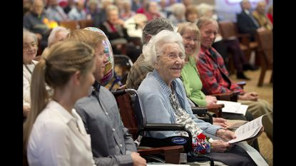 Vivian Myers smiles as she sits in the front row with members of her family at Carroll Lutheran Village Krug Chapel on Nov. 11, 2018 at a service and celebration commemorating the 100th anniversary of the end of World War 1 and the beginning of Veterans Day.