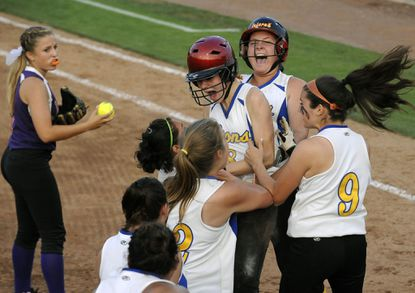 Liberty players surround Sammy Bost (red helmet) after she scored the game-winning run. Behind Bost are teammates MacKenzie Thompson (13) and Krysta Valenzia (9).