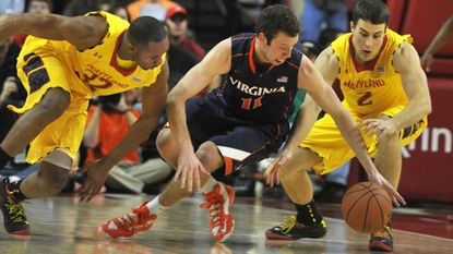 Maryland's Dez Wells, left, and Logan Aronhalt and Virginia's Evan Nolte chase a loose ball during a game in College Park in February 2013. The Cavaliers won, 80-69.