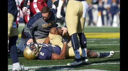 Navy associate athletic director for sports medicine Jim Berry, shown attending to an injured player during a football game in 2018, outlines the American Athletic Conference protocols for dealing with coronavirus.