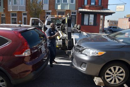 Charles Boyd tows a vehicle Thursday from South Potomac Street in Canton to make way for painting new bike lane lines on the street.