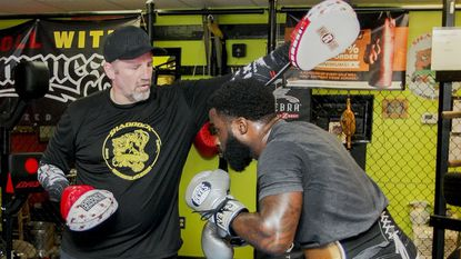 """Eldersburg resident John """"Bones"""" Shaddock, left, spars with Yahu """"Rock"""" Blackwell at Shaddock MMA Fitness. Blackwell is training for an upcoming fight in September."""