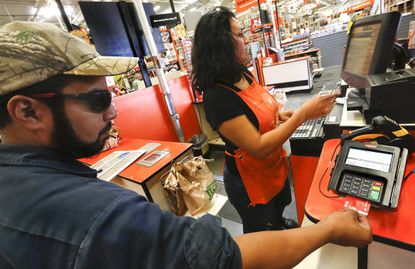 Robert Montanez, 39, left, inserts his debit card, equipped with an EMV chip, into an EMV reader while making a purchase at a Home Depot store in Burbank, Calif.