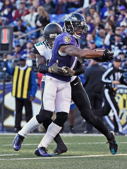 Ravens Chris Givens holds the ball across the goal line to score on a 14-yards catch in front of Jaguars' Josh Evans in the fourth quarter. The Ravens was defeated by the Jaguars by score of 22 to 20 at M & T Bank Stadium.