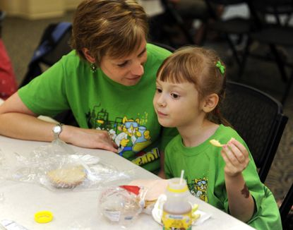 Laura Blood, left, talks with her daughter Lana Blood, 5, as she has lunch at the Arbutus branch of the Baltimore county public library. They live in Arbutus. The Arbutus branch is one of the library branches that are supplying free lunches to children this summer.