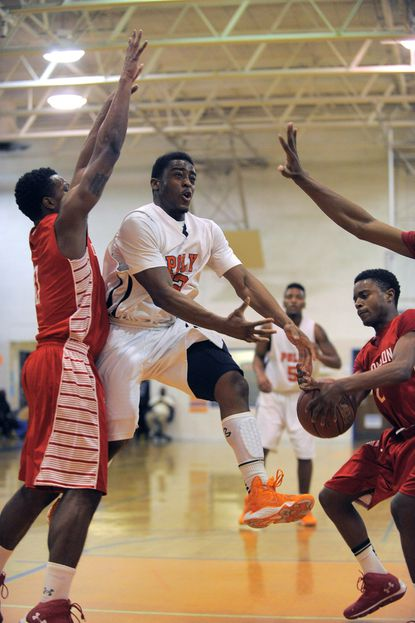 Poly Engineers' Darius Kelly (center) loses the ball to Edmondson Westside Red Storm guard Chaz Lassiter (right) while trying to drive past guard/forward Rashad Wattie (left) during boys' varsity basketball in this 2014 file photo.