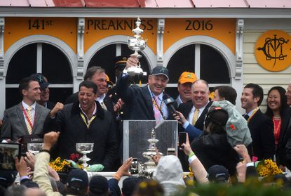 Sol Kumin pumps his fist as owner Matt Bryan holds the Woodlawn Vase aloft after Exaggerator wins the Preakness.