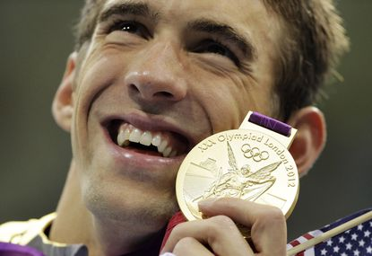 Michael Phelps poses with his gold medal for the men's 4x200-meter freestyle relay swimming final at the Aquatics Centre in the Olympic Park during the 2012 Summer Olympics in London. If the Rio de Janeiro Olympics were held today, the United States would win the most medals and the most gold medals, according to one projection system. Phelps would collect five more gold medals and a bronze, bringing his overall total to 28 with a career gold-medal haul to 23.