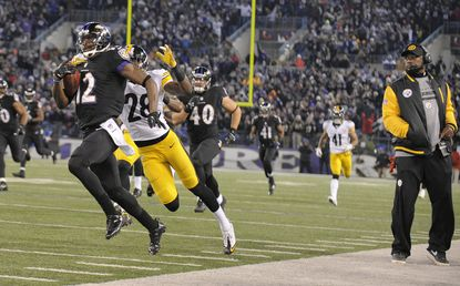 Ravens' Jacoby Jonesreturns akickoff in the third quarter as Pittsburgh head coach Mike Tomlin jumps off the field of play tothe sideline on Nov. 28, 2013.