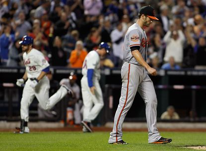 Orioles pitcher Jake Arrieta looks on as Ike Davis rounds the bases after hitting a sixth-inning grand slam.