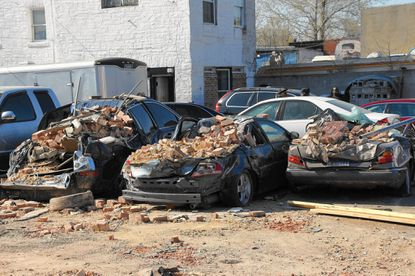 Cars damaged by debris from a fallen building on North Arlington Avenue in West Baltimore