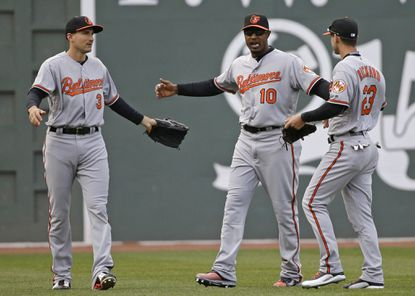 Baltimore Orioles' Ryan Flaherty (3), Adam Jones (10) and Joey Rickard (23) celebrate their 9-7 victory over the Boston Red Sox in a baseball game at Fenway Park, Monday, April 11, 2016, in Boston.