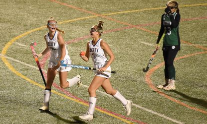 Liberty's Riley Pardoe carries the ball back up the field after scoring the Lions' fifth goal of the game, while sharing the joyous moment with teammate Maggie Heffler, left, in a 5-0 win over Patuxent during a 1A state semifinal field hockey game at Paint Branch High School on Thursday, November 7.