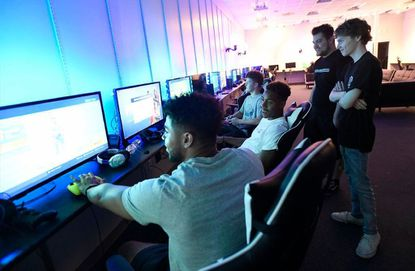 Shawn Mullins and Isaiah Rushe, right, gaming experts on the staff of Battleground Event Center look on as, from left, Anthony Murray, 19, of Taneytown, Gabe Goodrich, 18, of Westminster, and Parker Warehime, 15, of Taneytown participate in a Fortnite tournament at Battleground Event Center in TownMall of Westminster Friday, July 5, 2019.