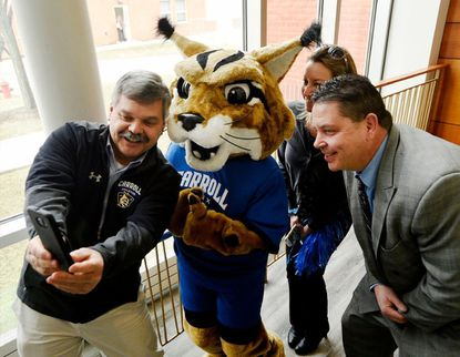 Carroll Community College women's soccer head coach Bill Warburton, left, and volunteer assistant coaches Michelle Shepard and Steve Berry take a photo with the Carroll Lynx during a celebration unveiling the new mascot Wednesday, Feb. 27.