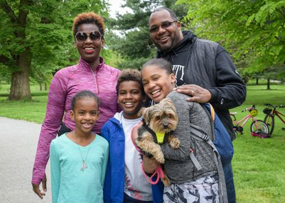 The Wesby family poses for a portrait together in Patterson Park. From left, Melissa, Lydia, Mitchell, Olivia (who's holding their dog Brooklyn), and John Wesby stand together near the park's entrance. Like a lot of parents right now, John and Melissa Wesby are balancing a full time work schedule with making sure their kids stay up to date on their school assignments. 5-5-2020