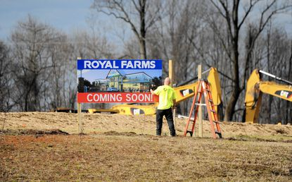 A worker puts up a sign Thursday afternoon on the location where a new Royal Farms is under construction along Route 24 near Forest Valley Drive.