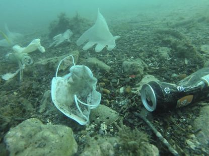 This photo taken on May 21, 2020 and provided by environmental group Operation Mer Propre (Operation Clean Sea) shows plastic gloves and face masks and other wastes on the floor of the Mediterranean Sea off Antibes in southern France. A French environmental group is trying to raise awareness and clean it up. (Operation Mer Propre via AP)