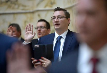 Sen. Michael Hough (R-District 4) raises his hand as he is sworn in on the opening day of the Maryland General Assembly in Annapolis on Wednesday, Jan. 9, 2019.