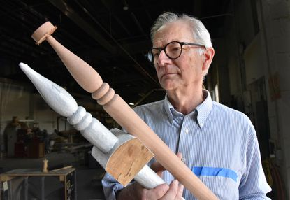 Mark Supik compares an original painted baluster from a Roland Park home with a replica made from sapele wood in his shop.