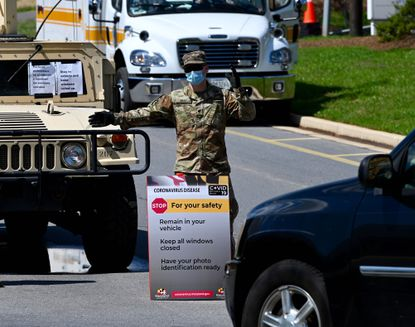 A Maryland National Guardsman directs traffic coming in the the coronavirus testing at the Glen Burnie VEIP station.
