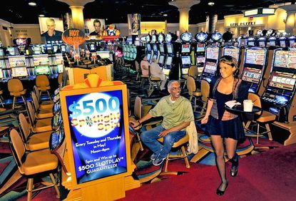 Beverage server Nicole Kinsey walks by Reginald Green of Philadelphia, who was ebullient about winning after playing the slots for the first time at Hollywood Casino in Perryville.
