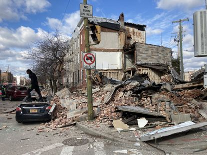 A tow truck operator clears bricks from the roof of a car that sustained damage from a building collapse in Pigtown on Jan. 17, 2021.