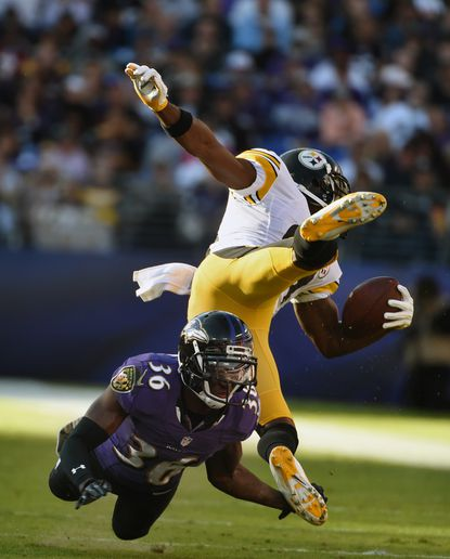 Ravens' cornerback Tavon Young trips up Steelers wide receiver Antonio Brown in the third quarter. Young limited Brown's production for much of Sunday's game.