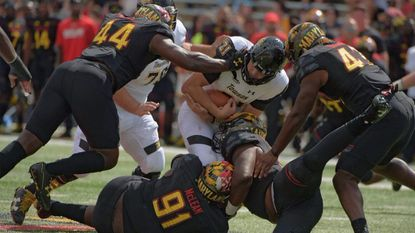 Maryland defensive lineman Andrew Isaacs (44), linebacker Jalen Brooks (top left), defensive lineman Keiron Howard (below) and defensive lineman Adam McLean (91) swarm Towson Tigers quarterback Ryan Stover as the pocket collapses against Towson on Saturday, Sept. 9, 2017.