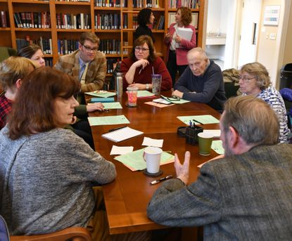 A group listens to one of the participants during the table discussion on the lesson regarding Baruch Spinoza's influence on contemporary Jewish-Christian relations at the Institute for Islamic, Christian, and Jewish Studies in Towson.