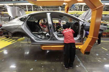In this March 14, 2014 photo, assembly line workers build a 2015 Chrysler 200 automobile at the Sterling Heights Assembly Plant in Sterling Heights, Mich. If the wider auto tariffs are imposed, industry experts say they will disrupt a decades-old symbiotic parts supply chain, raise vehicle prices, cut new-vehicle sales, cost jobs in the U.S., Canada and Mexico, and even slow related sectors of the economy.