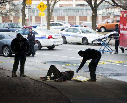 A victim of a shooting lies on the ground along Centre Street under I-83 awaiting medical attention.