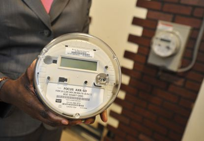 Jeannette M. Mills, vice president and chief customer officer for BGE, holds a smart meter.