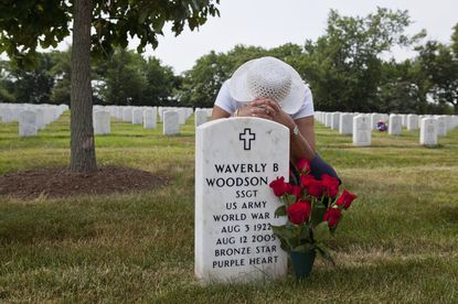 In this undated photo provided by Linda Hervieux, Joann Woodson kneels at the gravesite of her husband, Cpl. Waverly B. Woodson Jr., at Arlington National Cemetery in Arlington, Virginia. Members of Congress on Tuesday, Sept. 8, 2020, said Woodson, a Black Army medic who saved dozens of wounded troops on the beaches of Normandy on D-Day despite being severely wounded himself, deserves the Medal of Honor, as they announced legislation to posthumously award it to him. (Linda Hervieux via AP, File)