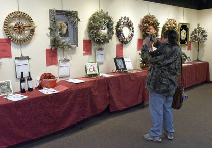 Crystal Piser photographs entries in the Carroll County Arts Council Festival of Wreaths in 2017. This year's Festival of Wreaths runs Friday through Dec. 8.