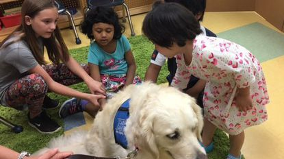 Point Pleasant Elementary School fifth grade helper Kayla Ciccarelli and primary autism students Manha Maheen and Kana Uehara meet therapy dog Jessie of Caring Canines.