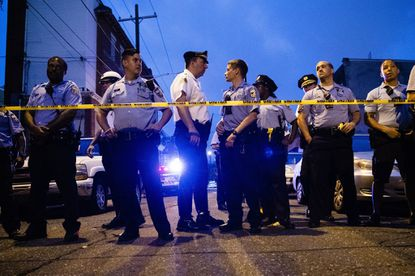 Six police officers wounded after gunman opens fire in Philadelphia, and 2 freed after being trapped in house in standoff