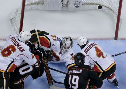 Ducks forward Corey Perry slips the puck past Flames goalie Karri Ramo in overtime to give Anaheim a 3-2 victory in overtime.