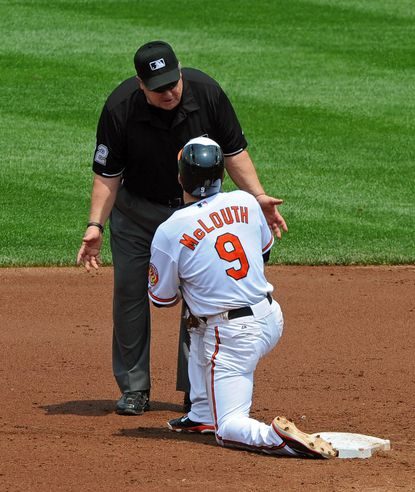 Second base umpire Joe West explains to Nate McLouth why he was called out on a stolen base attempt in the third inning Wednesday afternoon.