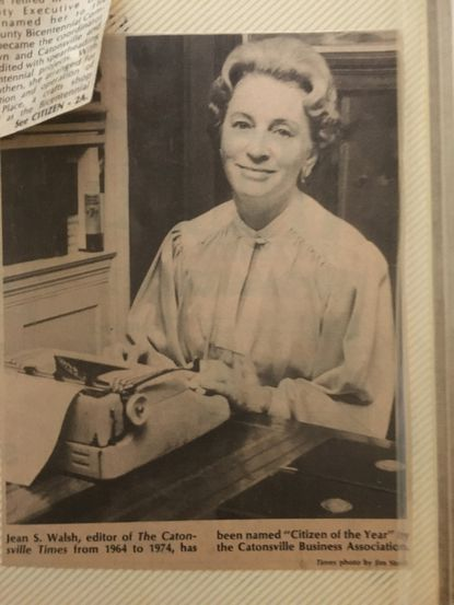 A newspaper clipping from an article in the Oct. 20, 1977 issue of the Catonsville Times shows Jean Walsh at her typewriter. Walsh was named Citizen of the Year by the Catonsville Business Association in 1977 for her community work and strides to document Catonsville history.