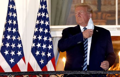 U.S. President Donald Trump removes his mask upon return to the White House from Walter Reed National Military Medical Center where he was treated for COVID-19 earlier this week.