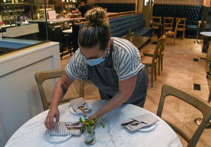 Allison Abel, a server at Cookhouse in Bolton Hill, sets a table in July. Labor unions and environmental groups are calling on Gov. Larry Hogan to issue rules to protect workers during the pandemic.